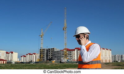 The chief is talking on the phone on the background of the construction of an apartment house