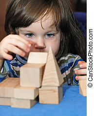The child - architect. The girl collecting a design from...