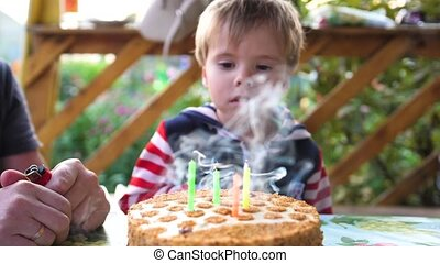 the child blows out the candle on the cake in his birthday...