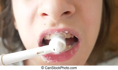 The child cleans his teeth in front of a mirror, girl teenager brushes teeth with electric toothbrush, close-up, slow-motion shooting