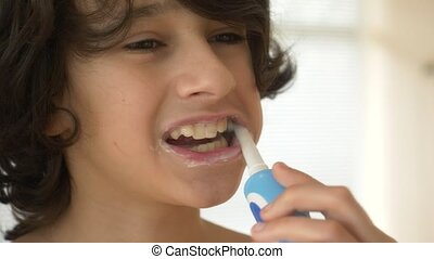 The child cleans his teeth in front of a mirror in 4k. boy teenager brushes teeth with electric toothbrush, close-up, slow-motion shooting