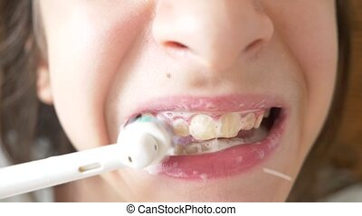 The child cleans his teeth in front of a mirror in. girl teenager brushes teeth with electric toothbrush, close-up, slow-motion shooting