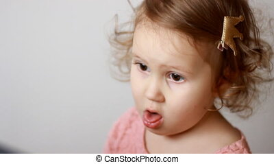 The child coughs. Portrait of a cute little girl close-up. The concept of cough, colds, viruses.