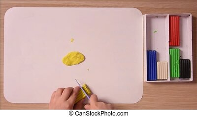 The child cuts off a piece of a stack of yellow plasticine for crafts, close-up, top view
