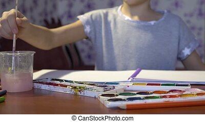 The child draws with a brush watercolor in the album....