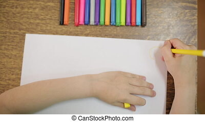 The child draws with a yellow felt-tip pen on a white sheet...