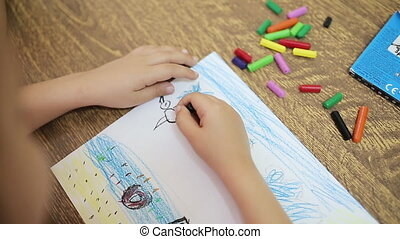 The child draws with black chalk for drawing makes an...