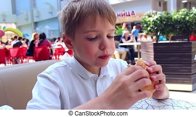 the child eats a cheeseburger in the cafe