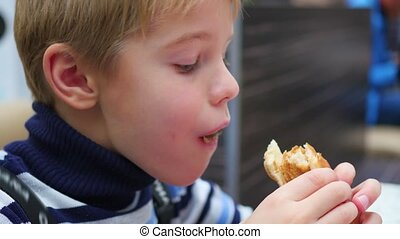 the child eats a scone with chicken in the fast food restaurant