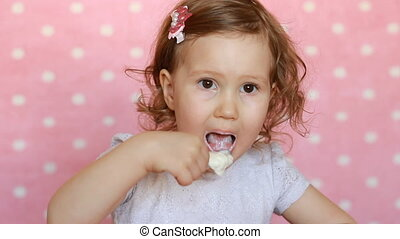 The child eats cottage cheese. Baby girl is eating a yogurt...