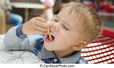 the child eats fried potato in fast food closeup