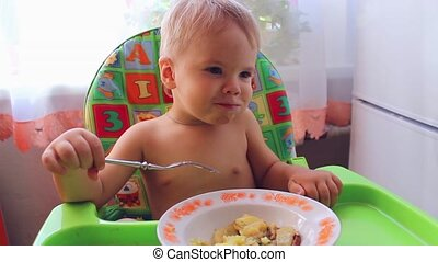 the child eats on a high chair - the child eats with a fork...
