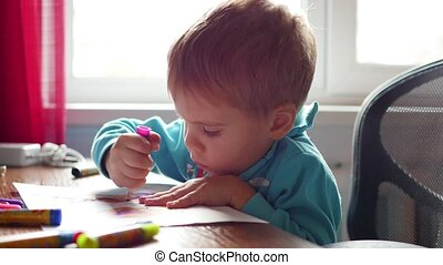 The child enthusiastically draws with crayons on a piece of paper. Preschool education