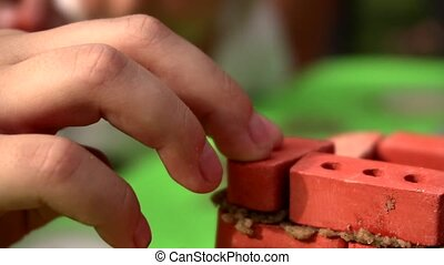 The child gently puts a small toy brick on its structure, close-up slow motion