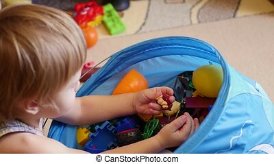 the child gets a toy from the basket for toys