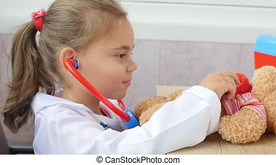 The child girl is playing doctor. A little girl with a...