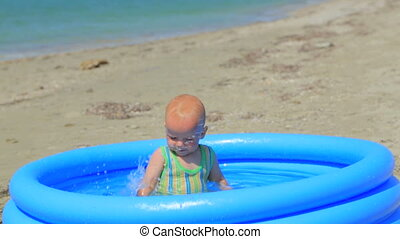 The child happily plays in the inflatable pool