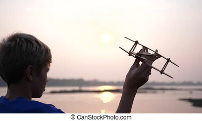 the child holds a plane in his hand against the setting sun,...