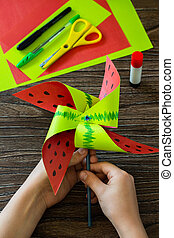 The child holds in his hands a paper wind mill. Fun toy watermelon windmill spinning on a wooden table. Children's art project, needlework, crafts for children.