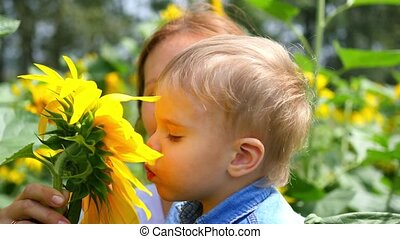 the child in his mother's arms playing with flower