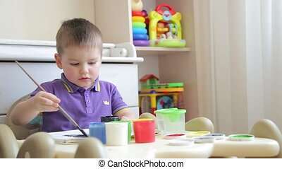 The child in kindergarten paints with a brush with colored paints