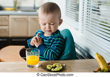 the child in the kitchen with juice and kiwi