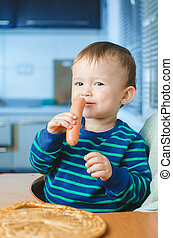 The child in the kitchen with sausage