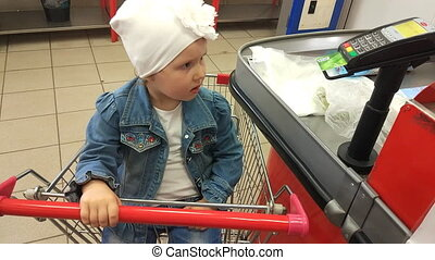 The child in the store buys food. girl is sitting in a trolley for food.