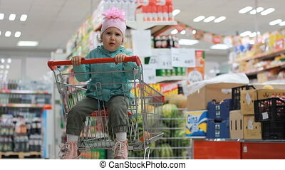 The child in the supermarket is sitting in a cart for food and points a finger at the product. The concept of shopping at the grocery store, discounts, sales