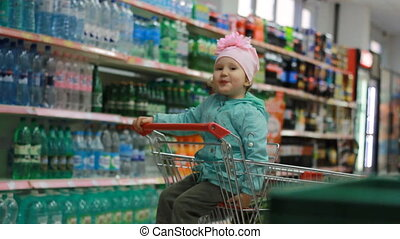 The child in the supermarket is sitting in a cart for food near shelves with drinks and stands with bottles and smiling. The concept of shopping at the store, discounts, sales.