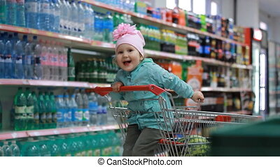 The child in the supermarket is sitting in a cart for food near shelves with drinks and stands with bottles, smiling, laughing and showing the language. The concept of shopping, discounts, sales