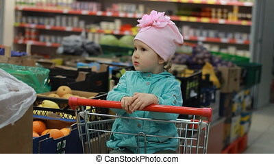 The child in the supermarket is sitting in a cart for food