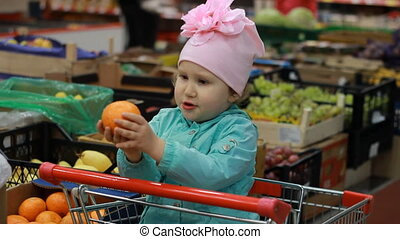 The child in the supermarket is sitting in a cart for food. The concept of shopping at the grocery store, discounts, sales.Fruit and vegetable market
