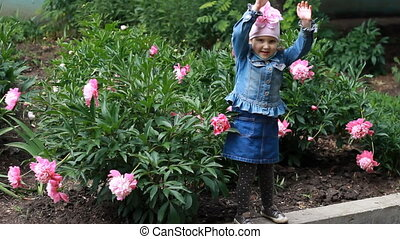 The child is doing exercises in the garden with peonies