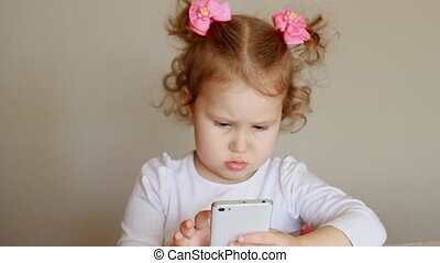 The child is holding a mobile phone, looking at the screen and touches his finger, plays downloaded application on a smart phone close-up