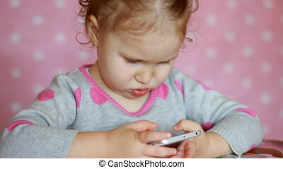 The child is holding a mobile phone, looking at the screen...