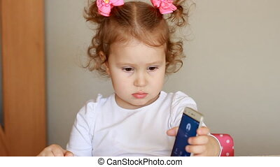 The child is holding a mobile phone, shows the screen smart...