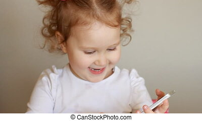The child is holding a mobile phone, looking at the screen and touches his finger, plays downloaded application on a smart phone close-up. Funny little girl smiling