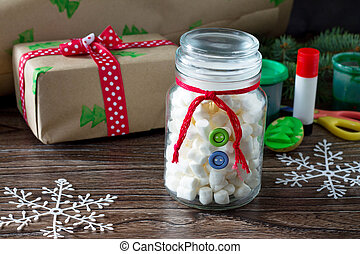 The child is making Christmas presents. Christmas gift box and snowman sweets. Made by own hands. Children's art project for children. Craft for kids.