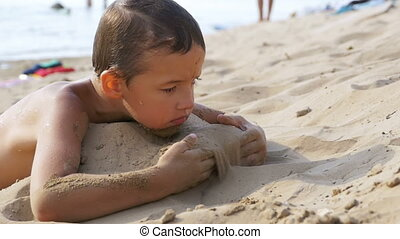 The Child is Playing with Sand on the Beach in Slow Motion