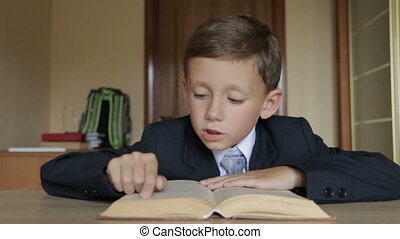 The child is reading a book. The boy's arms are 6-7 years...