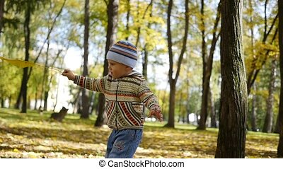 The child is spinning in autumn Park with yellow leaves,...