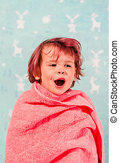 The child is wrapped in a towel.