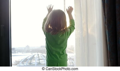 The child looks out the window and plays with the rays of the sun, knocks on the window. Expectation.