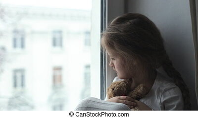 The child looks out the window in anticipation of his parents