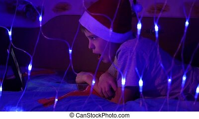 The child looks to the tablet lying on bed in hat santa.On the foreground, lights garlands