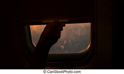 the child opens the shutter of the window on the airplane to see the sunset