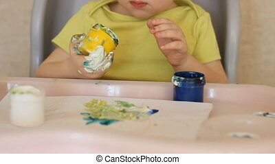 The child paints with his fingers.