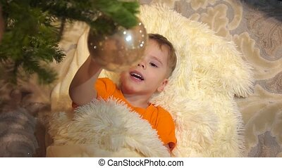 The child play in the children's room with Christmas tree. The boy lies on a white fluffy blanket. Happy childhood