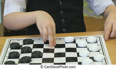 The child plays checkers in kindergarten indoors -...